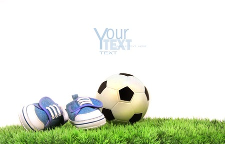 Childs shoes with rubber ball on grass against white background photo