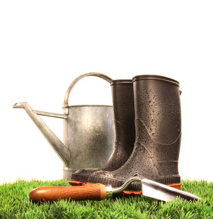 Garden boots with tool and watering can on grass