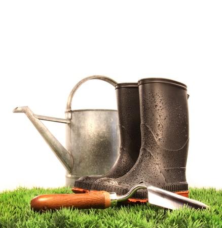 regando plantas: Jard�n botas herramienta con regadera y sobre la hierba Foto de archivo