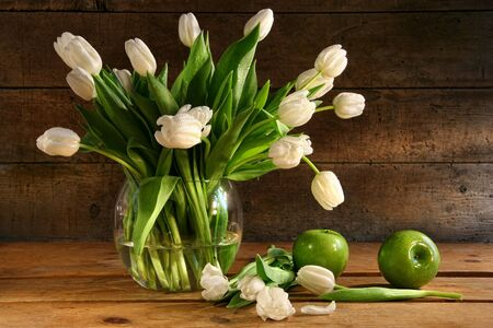 White tulips in glass vase with rustic wood background Stock Photo