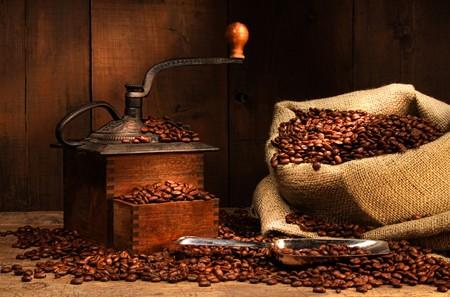 Antique coffee grinder with beans in burlap sack Archivio Fotografico