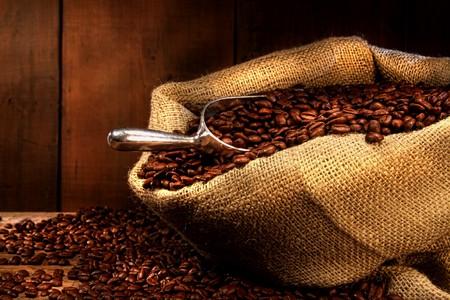 アンティーク木材の背景と黄麻布の袋のコーヒー豆