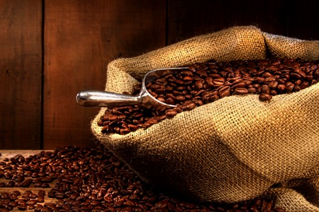 Coffee beans in burlap sack with antique wood background Stock fotó