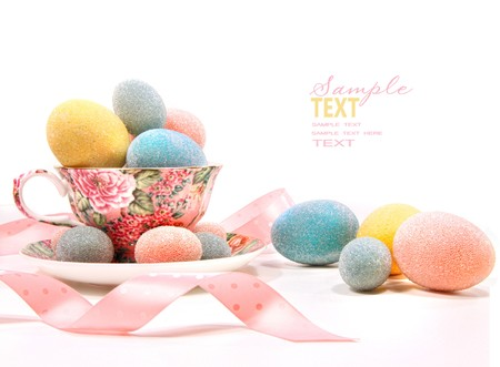 Brightly colored eggs in tea cup on white photo