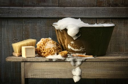 Old wash tub with soap on rustic bench Archivio Fotografico