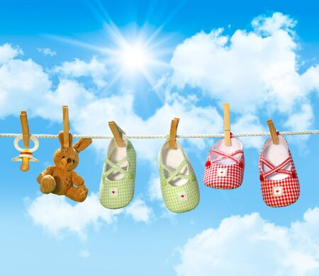 Baby shoes, pacifier and teddy bear on clothesline with blue sky
