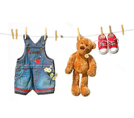 Childs clothes with teddy bear on clothesline on white photo