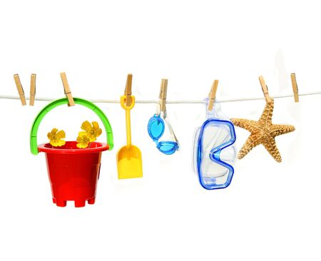 Child's summer toys on clothesline against white background Stock Photo - 4632218