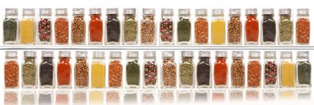 Assorted spices on two layer shelves against white background photo