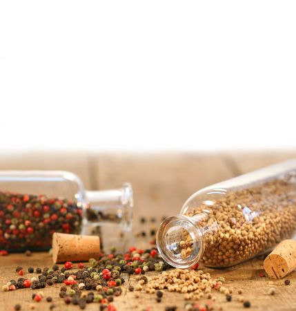 Bottles of spices on rustic wood table  photo