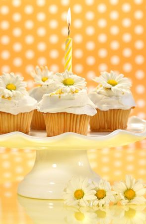 Cupcakes decorated with icing and little daisies on cake tray photo