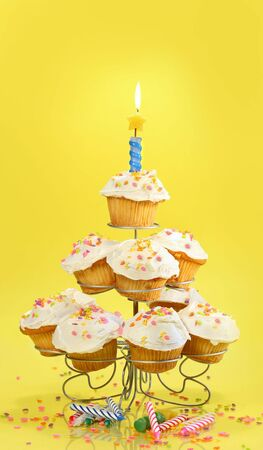 Cupcakes on multi-tiered stand with candle on yellow background photo