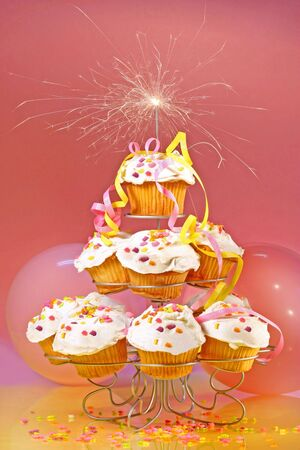 Cupcakes with sparkler on top against pink background photo