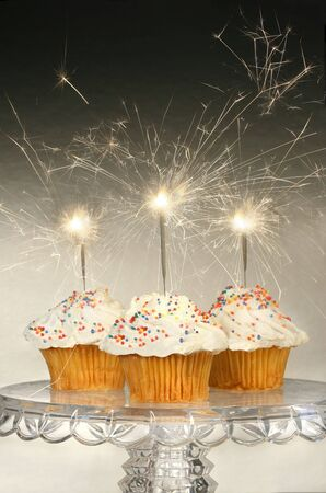 Cupcakes with sparklers on glass cake stand photo