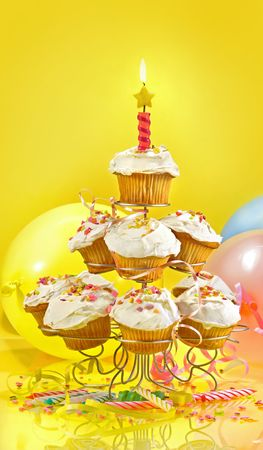 Lots of cupcakes on a muli-tiered stand against yellow background