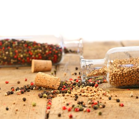 Peppercorns in glass bottles on rustic wood table photo