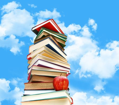 Pile of books and apple against blue sky with clouds Stock Photo