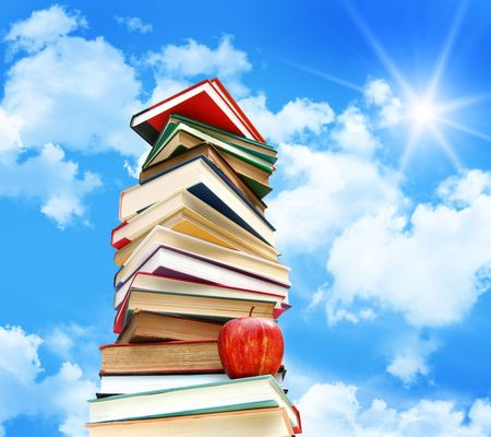Pile of books and apple against blue sky with sun and clouds Stock Photo