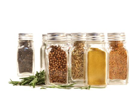Spice jars with fresh rosemary leaves against white background photo
