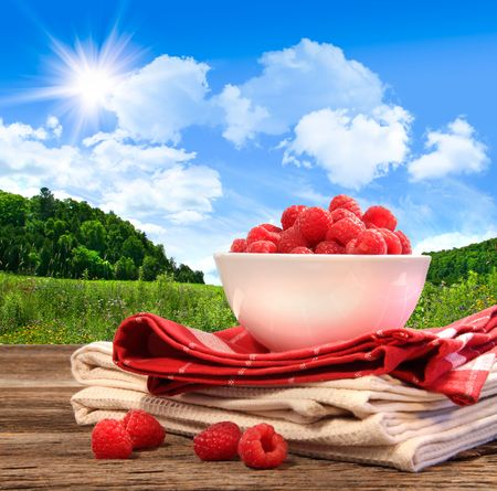 Bowl of raspberries on rustic table in a country setting photo