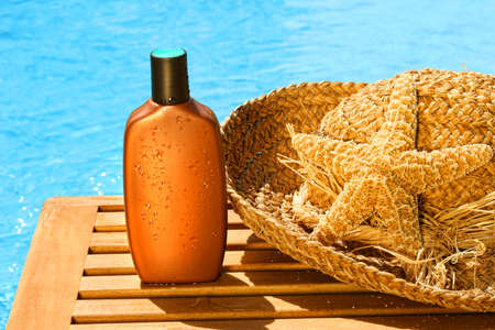 sun hat: Tanning lotion with sun hat by the pool