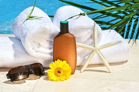 White spa towels and tanning lotion by the pool Stock Photo