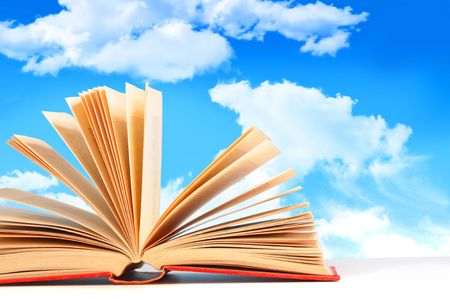 Open book on white surface against a blue sky Stock Photo - 5017047