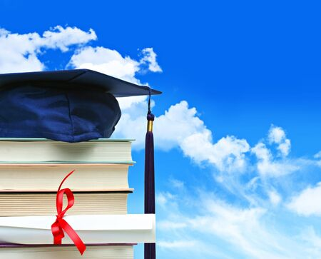 Stack of books with cap and diploma against blue sky photo