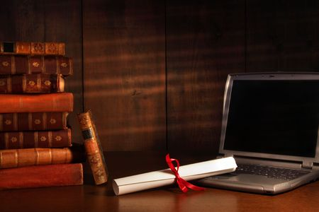 Antique books, diploma with laptop on school desk photo