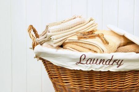 Clean towels in wicker basket with white wood background photo