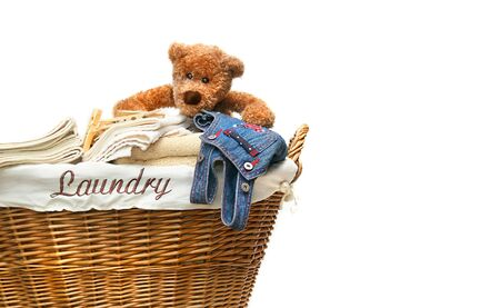 Laundry basket full of towels with teddy bear on white background photo