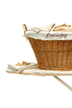 Laundry basket with towels on ironing board against white background Stock Photo