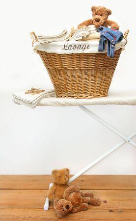 domestic task: Laundry basket with teddy bears on pine floor