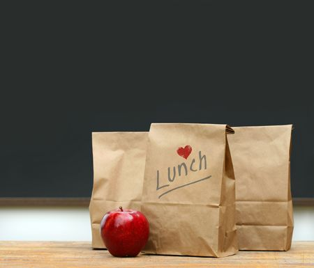 brown: Paper lunch bags with red apple on school desk