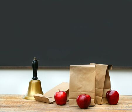 Paper lunch bags with apples and school bell on desk photo