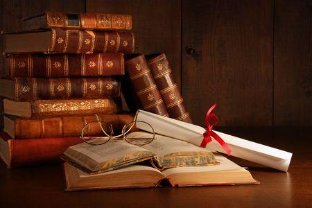 messy desk: Mont�n de libros antiguos con gafas de lectura en escritorio