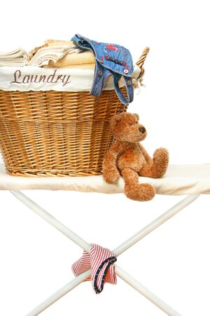 Teddy bear with laundry basket on ironing board against white background photo