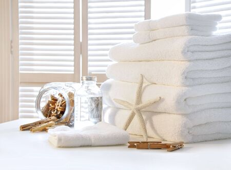 tela algodon: Mullidas toallas blancas en la mesa con puertas de persiana