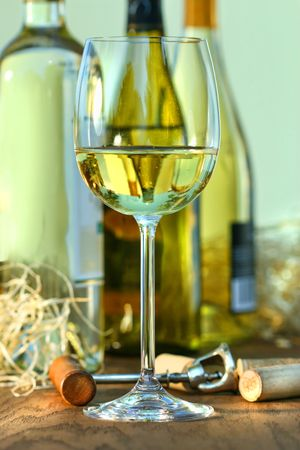 Glass of white wine with bottles on oak table photo