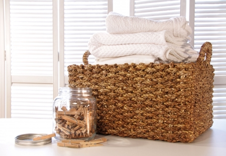warm cloth: Laundry basket with linens on table with clothespins in jar