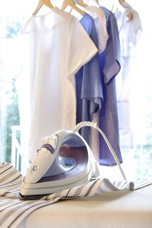 board: Iron on ironing board with clothes hanging in background Stock Photo