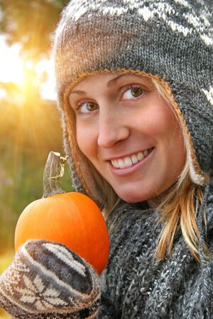 Young woman holding a pumpkin on an autumn day photo