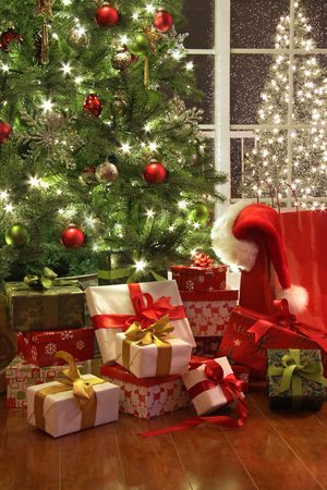 Brightly lit christmas tree with lots of gifts near window photo