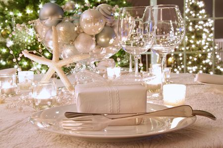 Elegantly lit  holiday dinner table with wine glasses and white ribboned gift Stockfoto