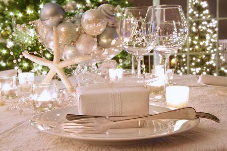 cena navidad: Tabla de cena de vacaciones elegantemente iluminadas con vasos de vinos y blanco arropan regalo