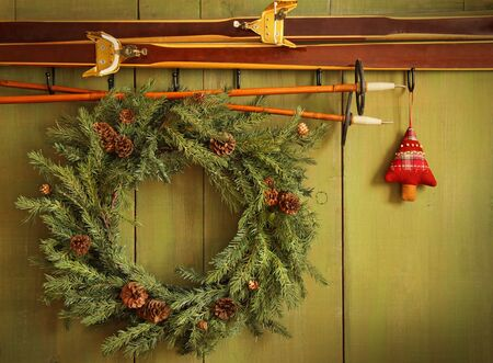 Old pair of skis hanging with wreath against green wood background photo