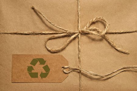 moving box: Brown shipping parcel tied with twine and a blank shipping tag for copy space