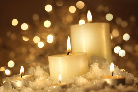 sparkly: Brightly lit candles in wet snow against sparkly background