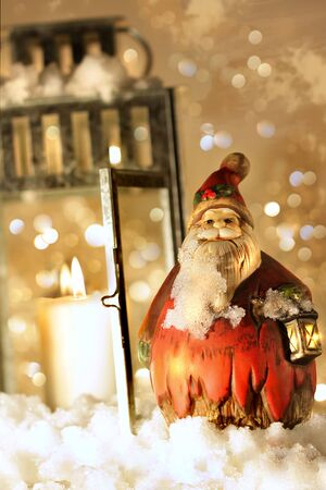Brightly lit lantern in the snow with little Santa photo