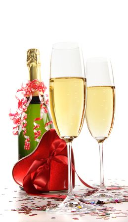 Glasses of champagne with red ribbon heart on white photo